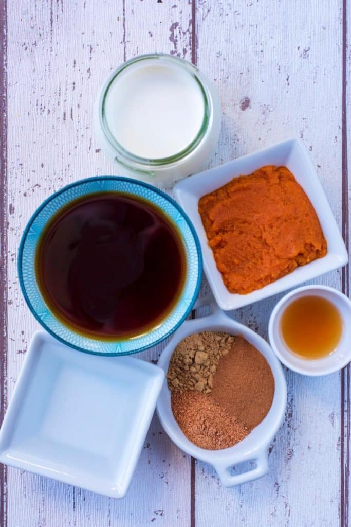 Bowls of maple syrup, pumpkin puree, milk, water and spices on a wooden surface