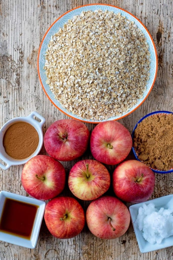 Seven red apples and a plate of oat on a wooden surface