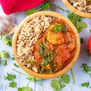 Prawn, Tomato and Coconut Curry and rice in a wooden bowl. Coriander leaf is scattered around it