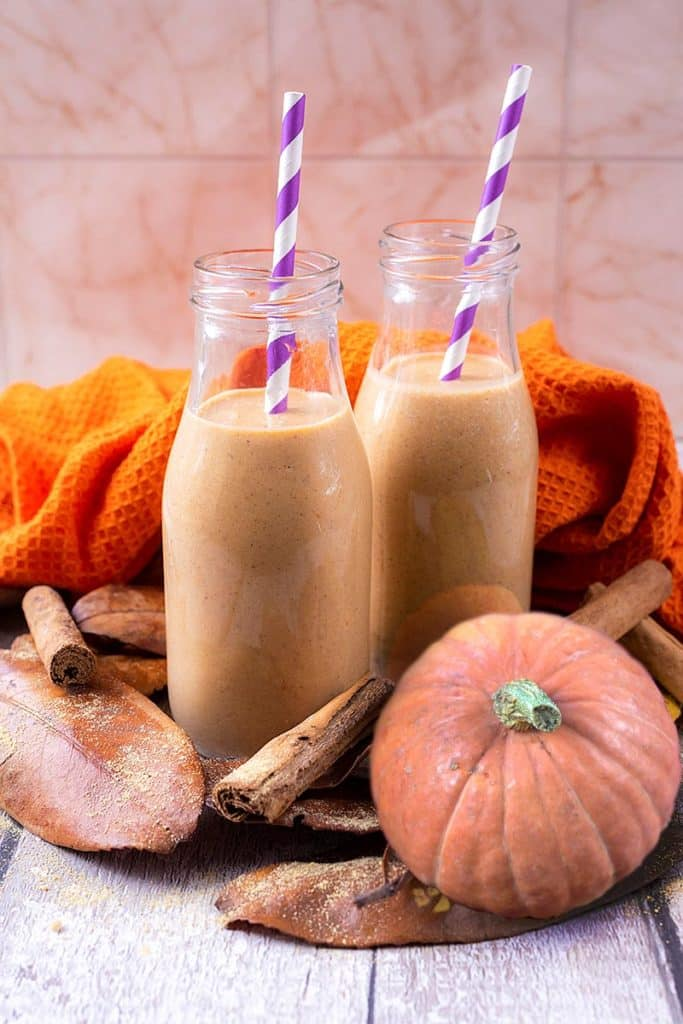 Two small milk bottles containing pumpkin smoothie with striped straws. A small pumpkin sits next to them