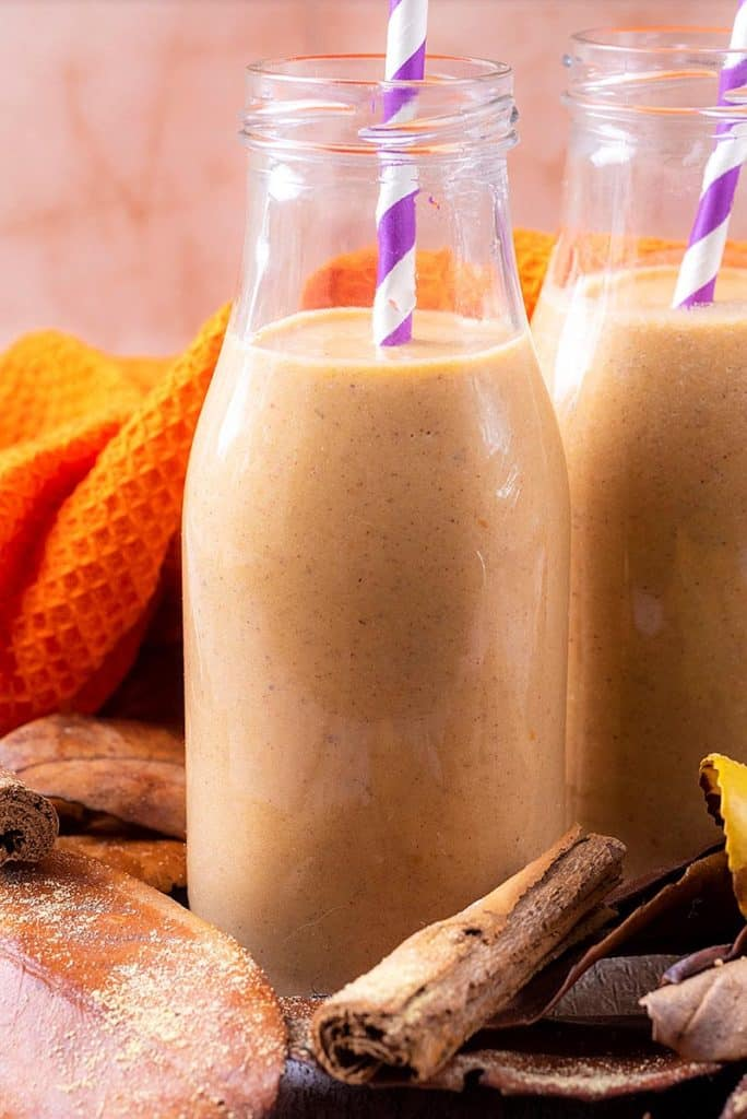 A glass bottle filled with pumpkin smoothie