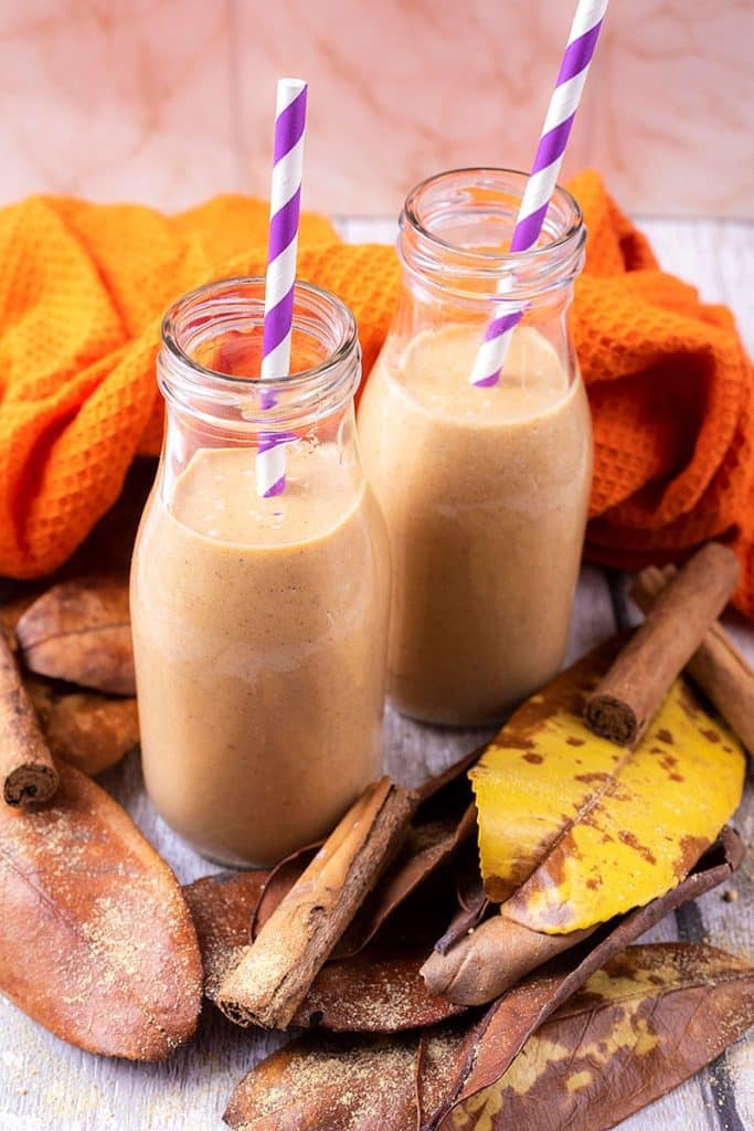 Pumpkin smoothie in two glass bottles surrounded by brown leaves
