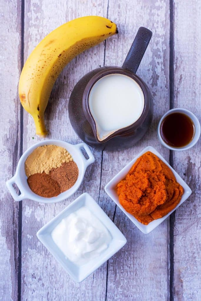 A jug of milk, a banana, some yoghurt, pumpkin puree, maple syrup and spices all arranged on a wooden surface
