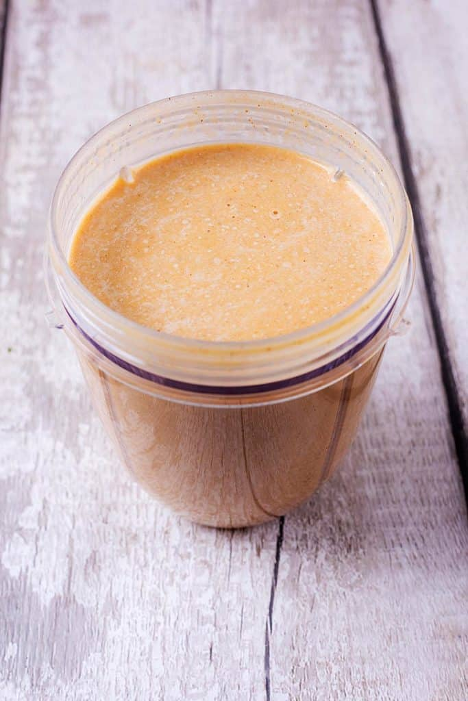 A blender jug containing a blended pumpkin smoothie
