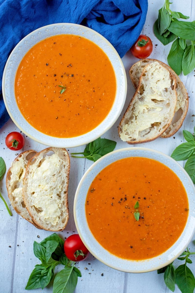 Two bowl of red pepper and tomato soup next to some slices of buttered bread