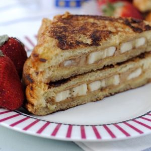 Stuffed French Toast on a red and white plate with two large strawberries
