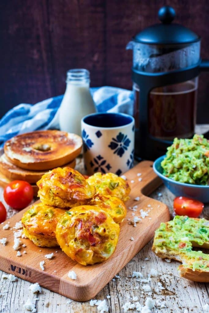 Breakfast Egg Muffins in front of a pot of coffee with bagels and mashed avocado