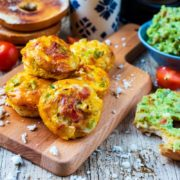 Breakfast Egg Muffins on a serving board in front of a pot of coffee