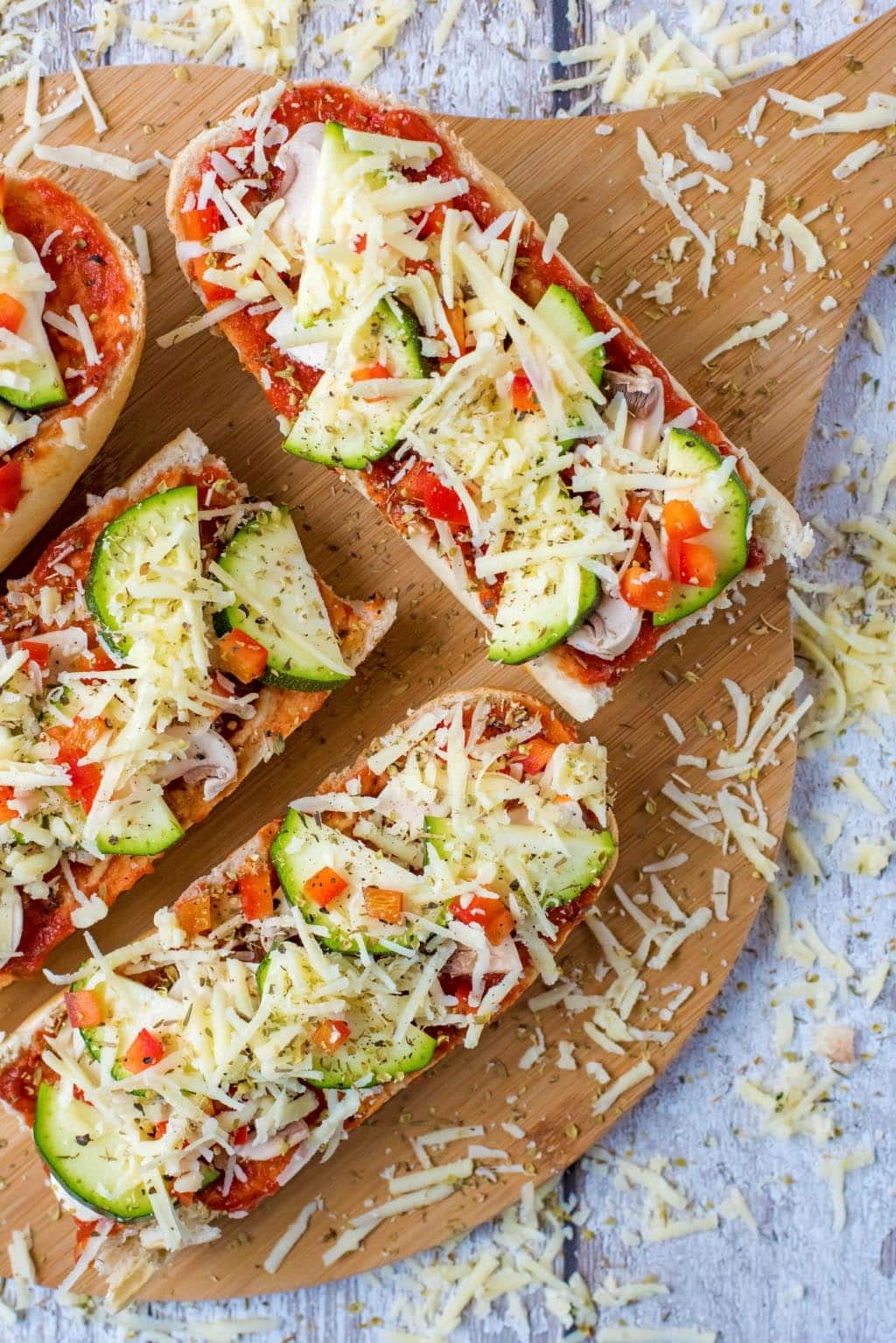 French bread pizzas on a serving board with grated cheese scattered around