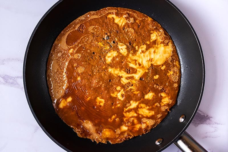A brown omelette cooking in a frying pan