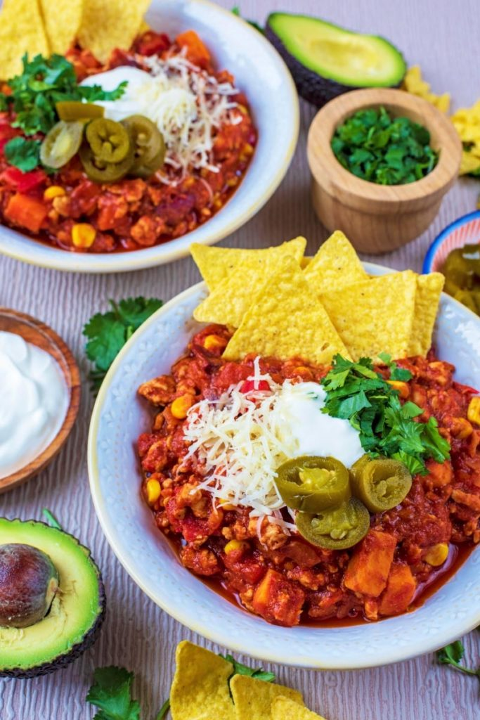 Chili in bowls with avocado, sour cream and cheese