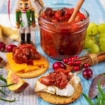 Christmas Chutney in a jar. Two cheese on crackers sit in front and grapes in the background