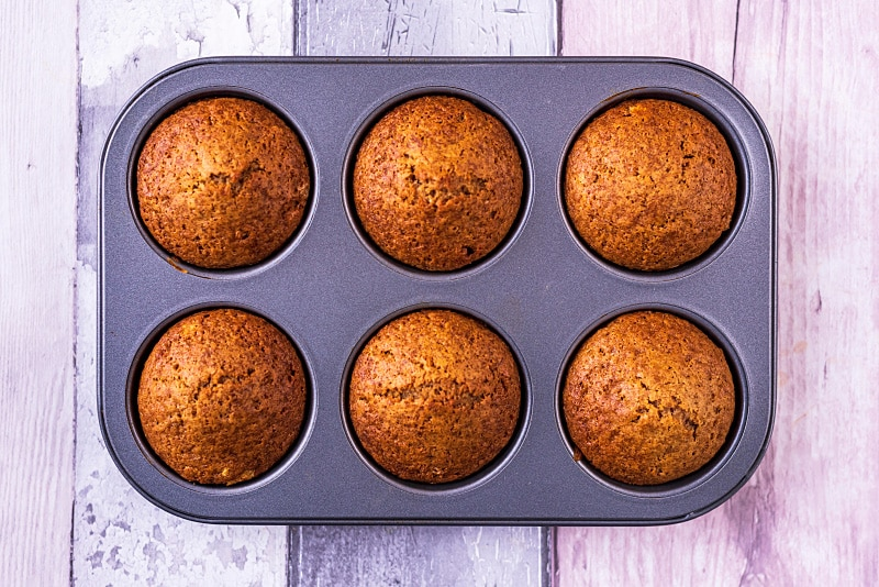 Six cooked cupcakes in a cupcake tin