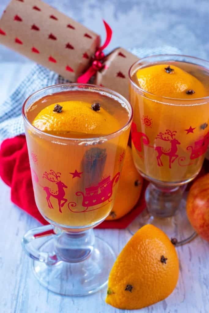 Two glasses of Mulled Hot Apple Juice with orange wedges and a Christmas cracker