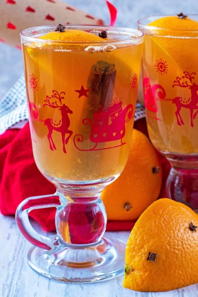 A cinnamon stick and orange segment in a Christmas glass