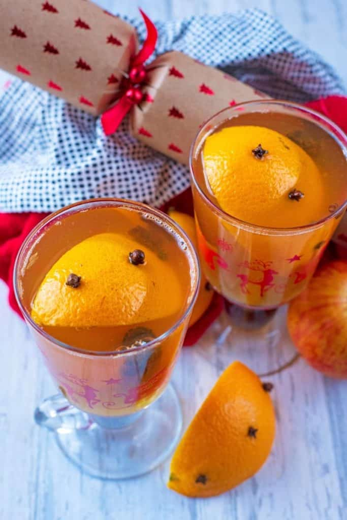 Clove spiked oranges floating in two glasses of Mulled Hot Apple Juice