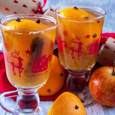 Christmas glasses containing Mulled Hot Apple Juice . An apple, cracker and red towel are in the background