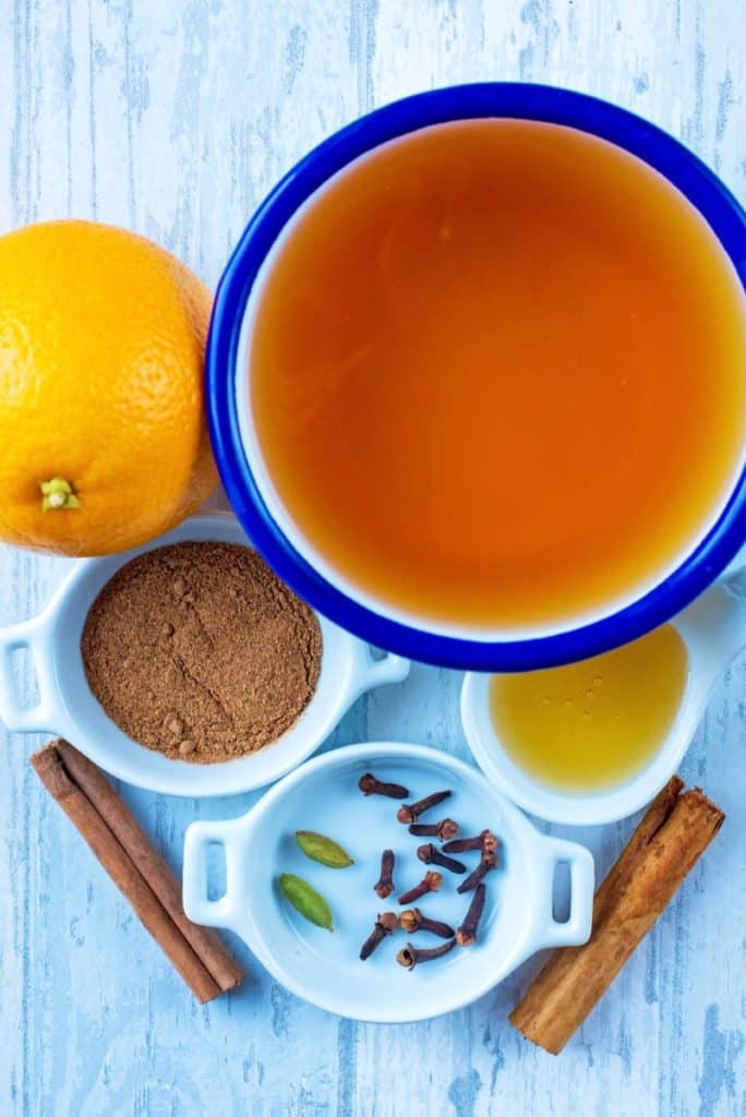 A bowl of apple juice, whole orange, honey and spices all on a wooden surface