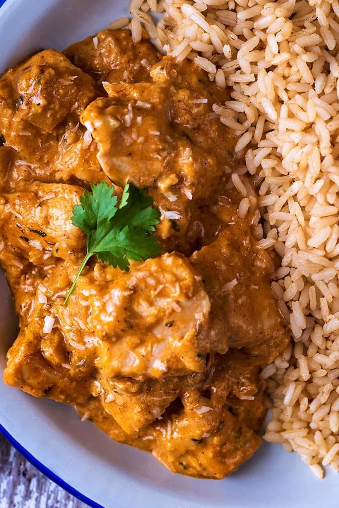 Chunks of chicken in a curry sauce with a cilantro leaf on top