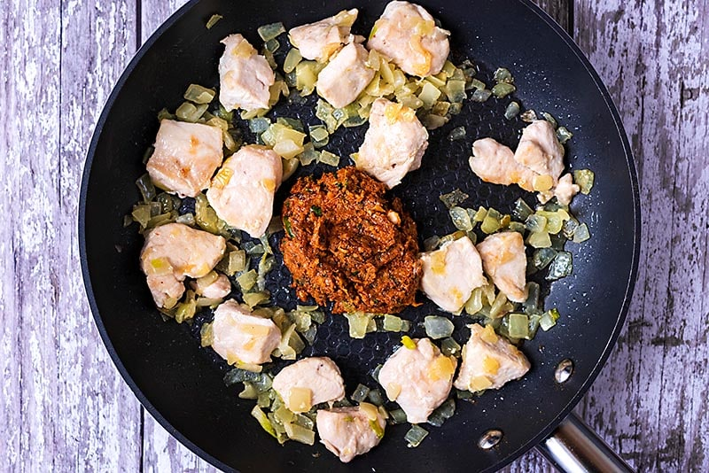 Cooked chicken chunks and chopped onion in a frying pan with curry paste