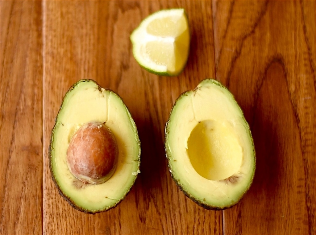 Cut avocado with a lime wedge
