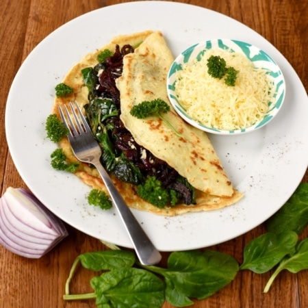 Caramelised Onion and Cheddar Savoury Pancakes on a wooden surface with spinach leaves