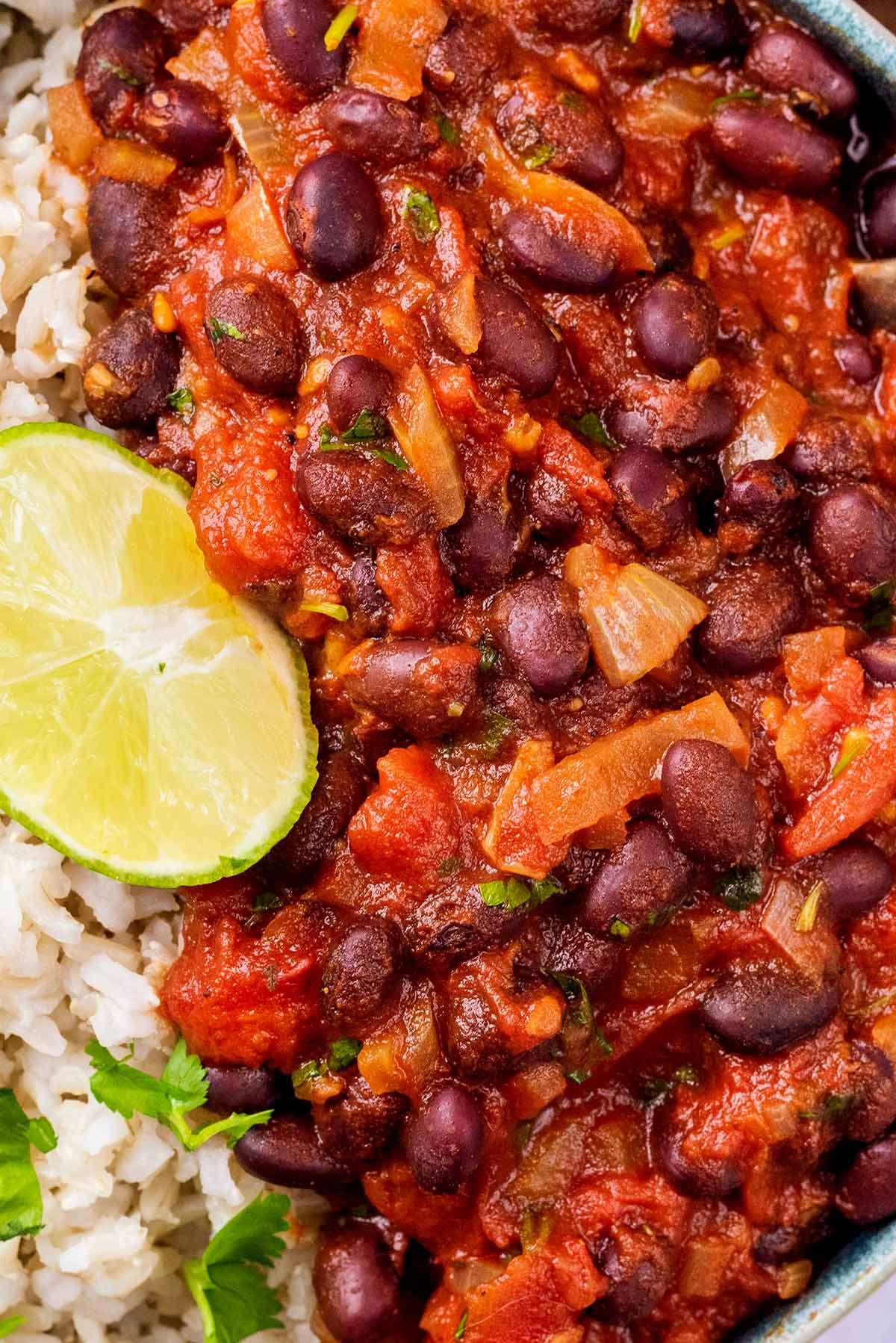 Black beans in a tomato sauce next to some rice with a lime wedge.