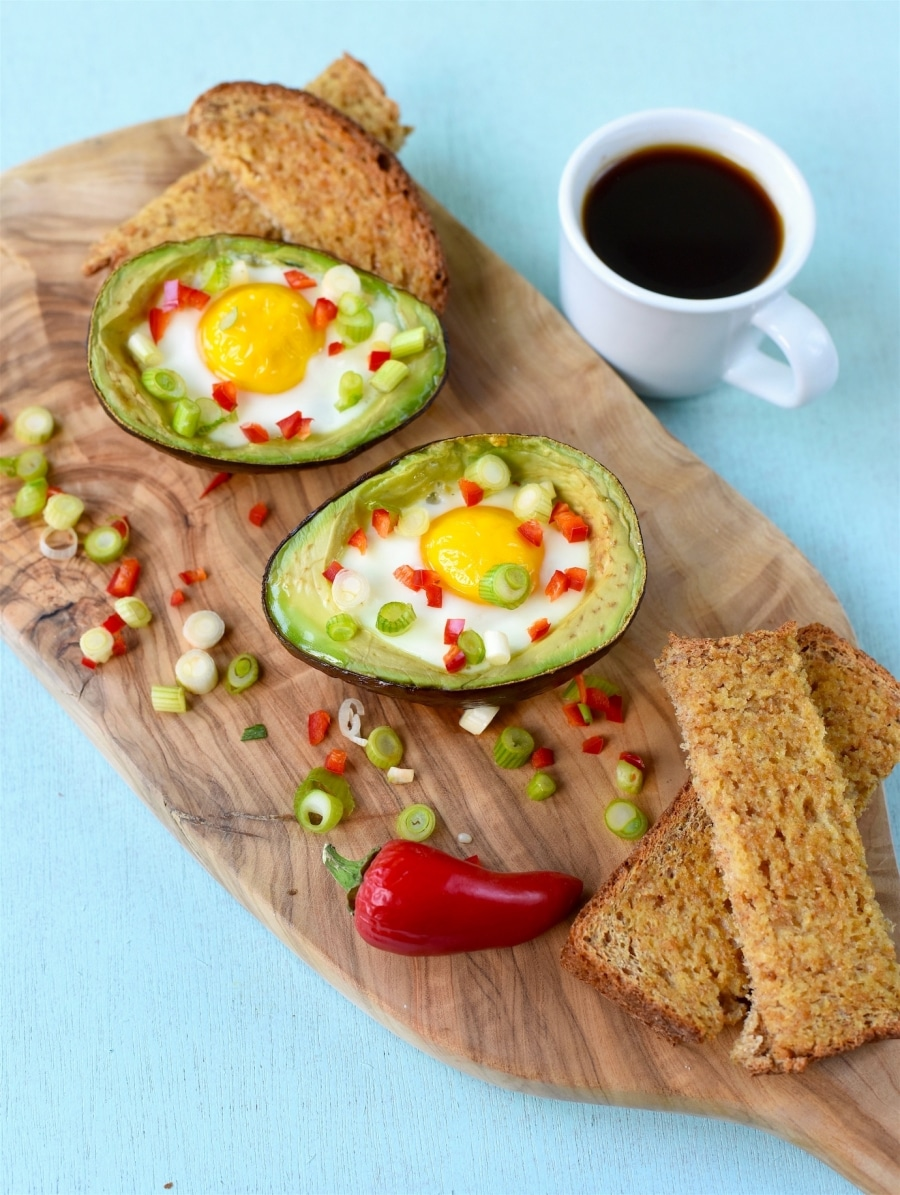 Eggs Baked in Avocado on a wooden serving board next to a cup of coffee