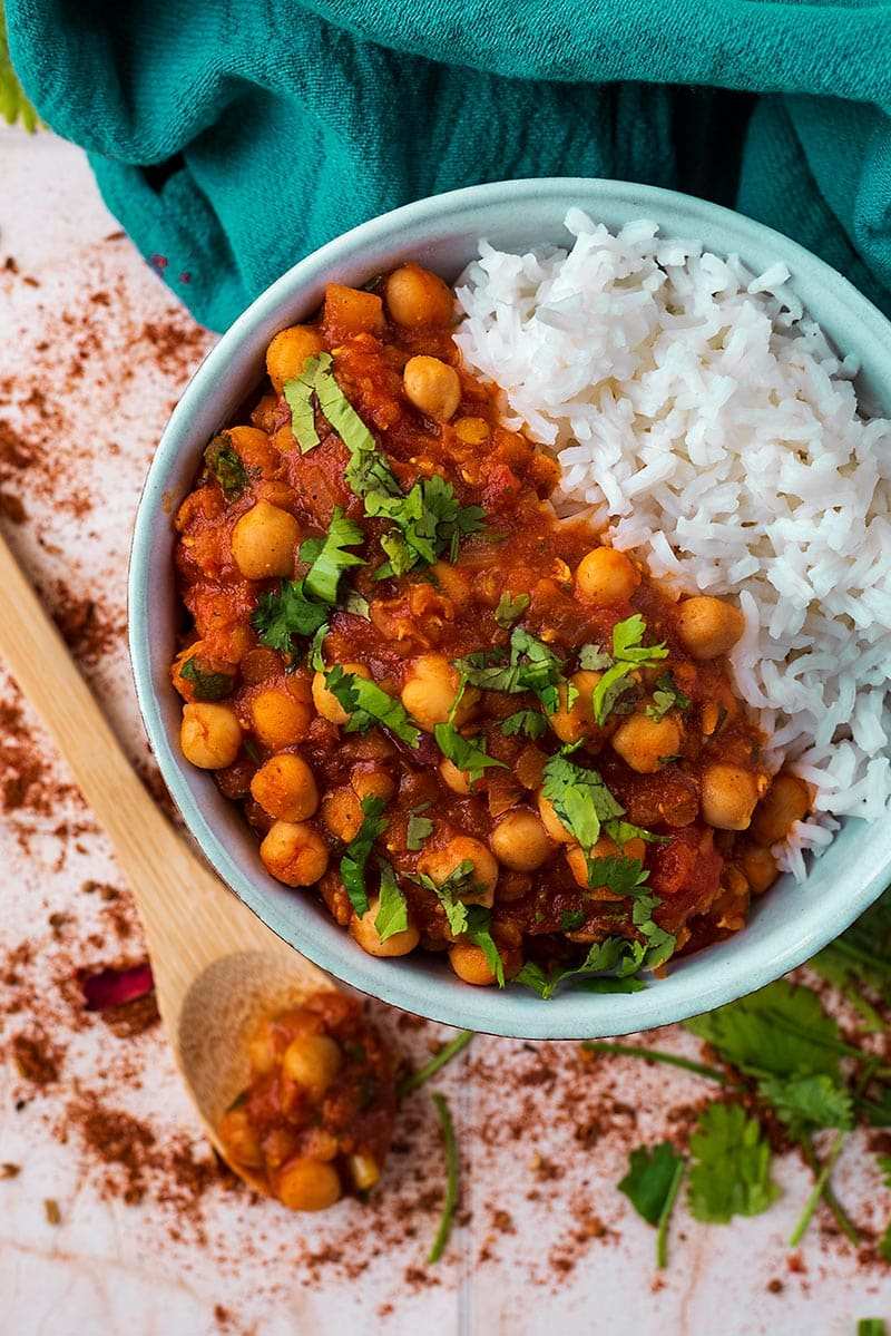 A bowl of Moroccan Chickpea Stew and rice next to a blue towel