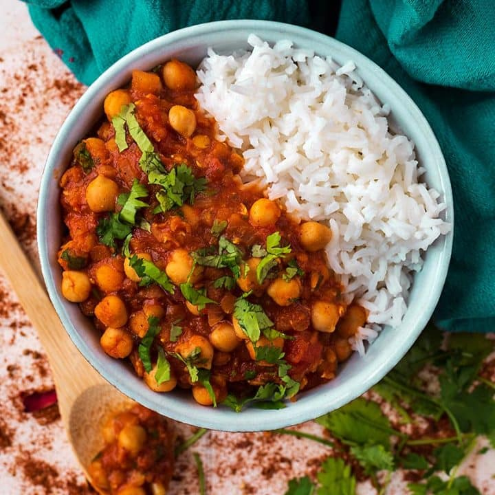 Moroccan Chickpea Stew in a bowl with rice surrounded by spices and chopped cilantro