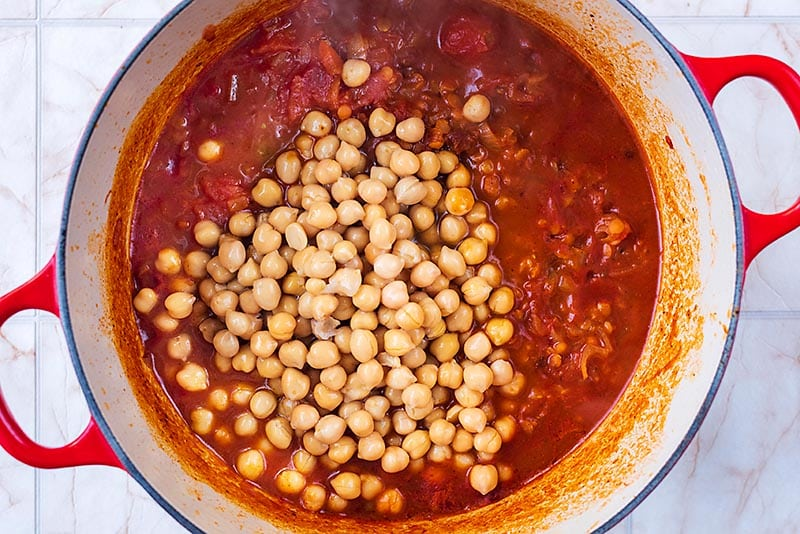 A large pan with a tomato sauce and chickpeas cooking in it