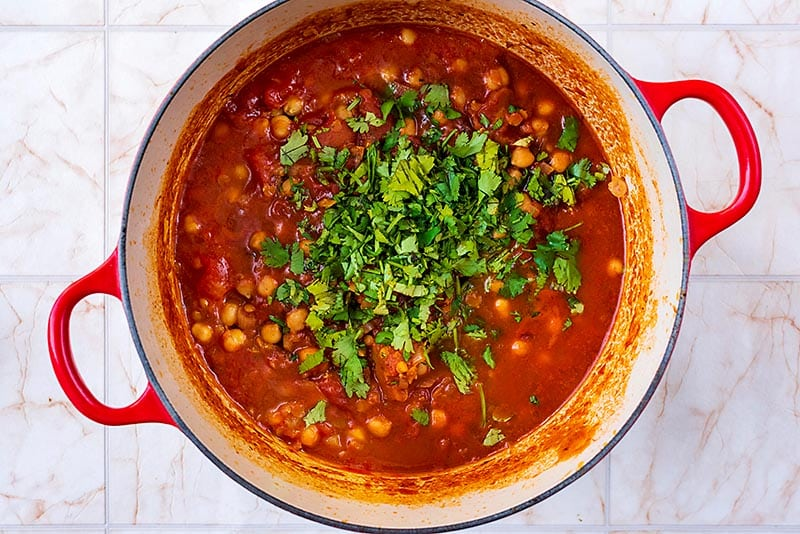 Chickpeas cooing in a tomato sauce with a large pile of cilantro on top