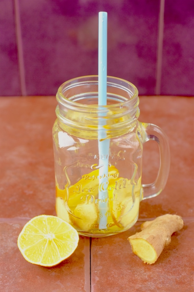 A mason jar full of water with slices of lemon and ginger in it