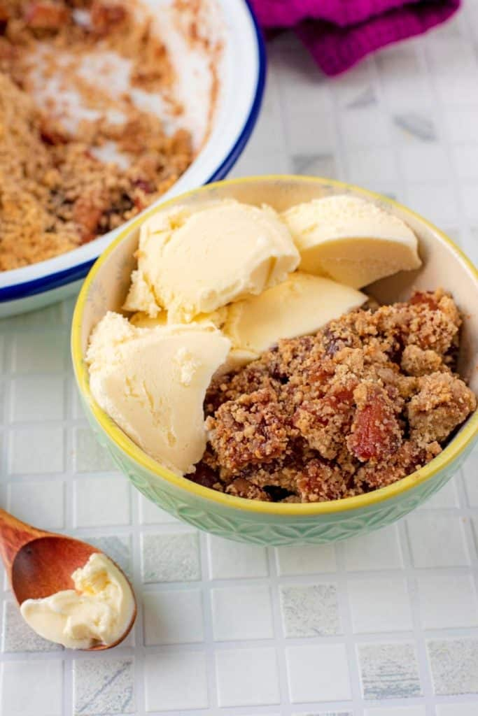 A bowl of Apple and Cherry Crumble with ice cream