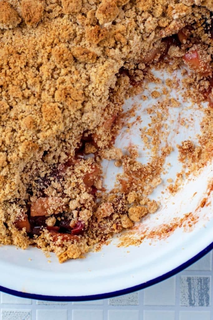 A dish of Apple and Cherry Crumble with a section removed