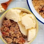 Apple and Cherry Crumble in a bowl with vanilla ice cream