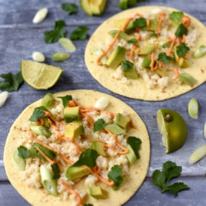 Two Crab and Avocado Tacos on a blue surface with lime wedges