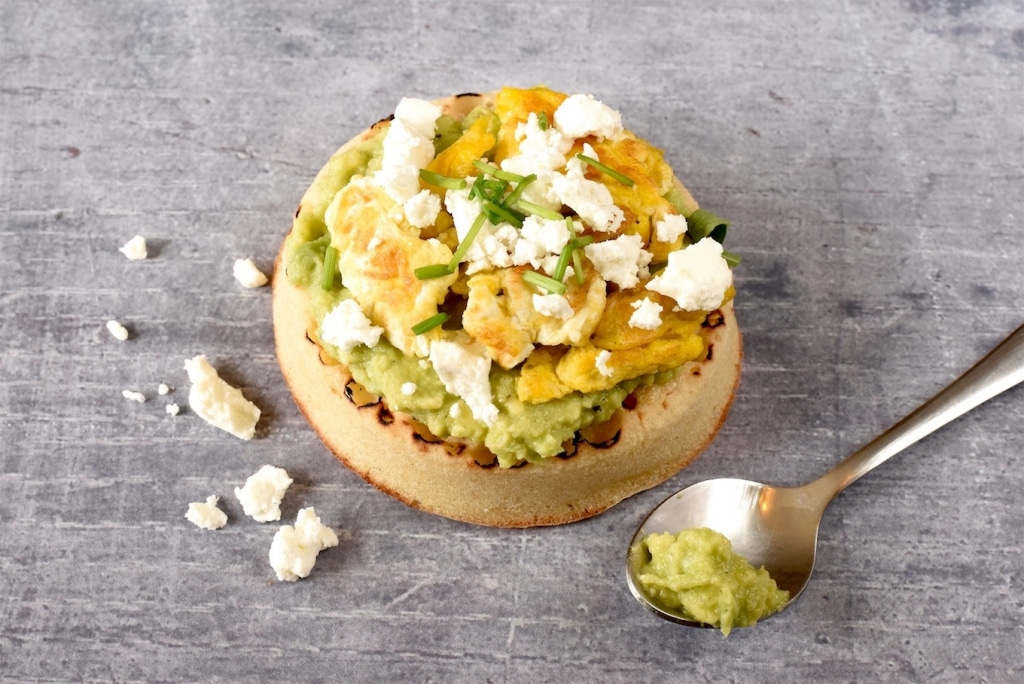 A Crumpet topped with avocado, egg and feta