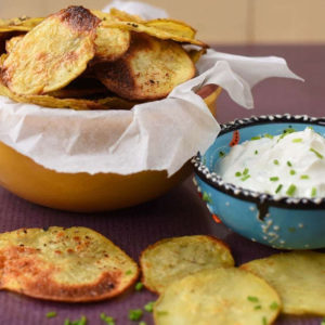 Homemade Garlic Crisps in a bowl next to a pot of dip