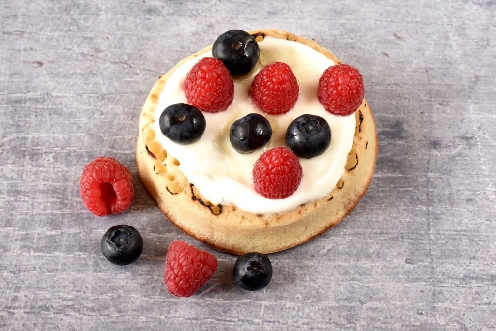 A Crumpet topped with greek yoghurt, blueberries and raspberries