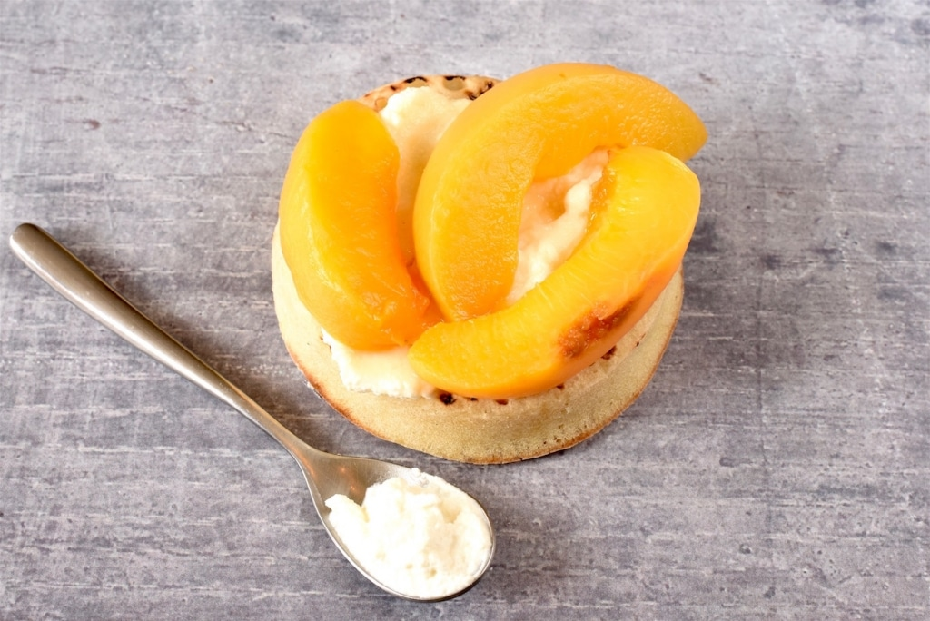 A Crumpet topped with ricotta, sliced peaches and honey