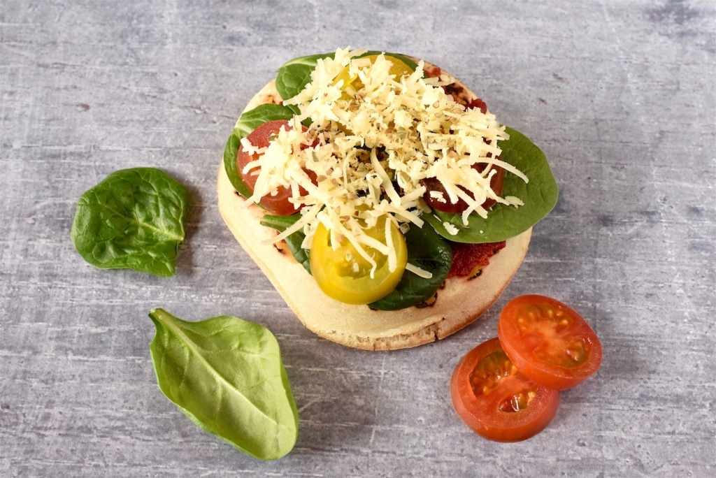 A Crumpet topped with cheese, tomato and spinach
