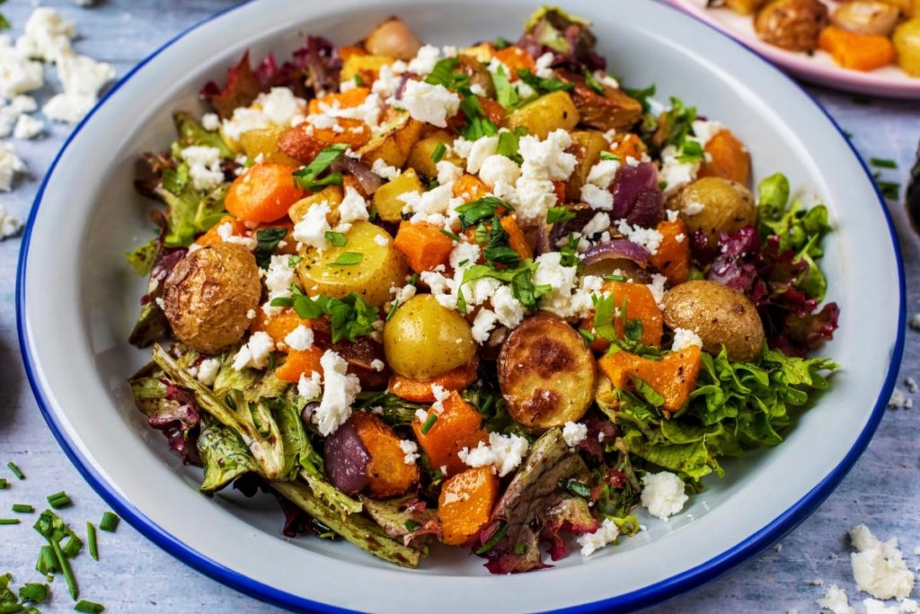 Salad leaves topped with roasted vegetables and crumbled feta cheese
