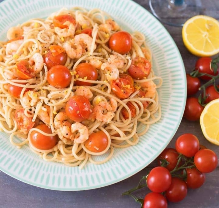 Tomato, Garlic and Prawn Spaghetti on a patterened plate next to cherry tomatoes on the vine