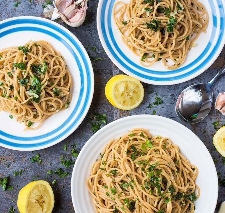 15 Minute Garlic and Herb Spaghetti on two patterned plates an a white bowl