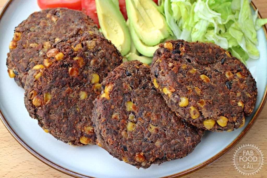 Four Bean Burgers on a plate with lettuce avocado and tomatoes