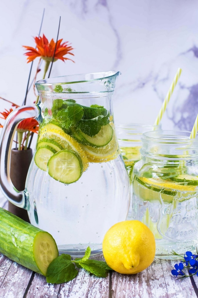 Sliced cucumber, mint leaves and lemon slices in a large jug of sparkling water