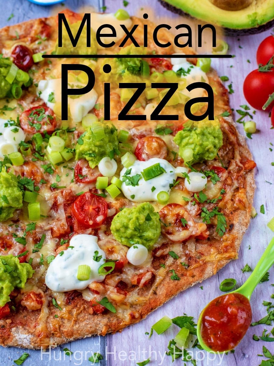 Mexican Pizza is a fusion of two of the best cuisines in the world. A crisp pizza base smothered in hot and smokey chunky salsa and then scattered with some tomatoes and cheese. Topped off with mashed avocado, sour cream and some onion and herbs. Is your mouth watering yet? #mexicanfood #italianfood #fusionfood #pizza #pizzarecipe #avocado