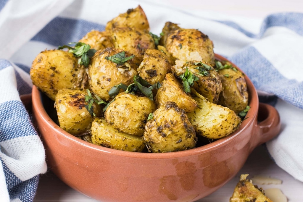 A bowl of cooked new potatoes topped with chopped herbs