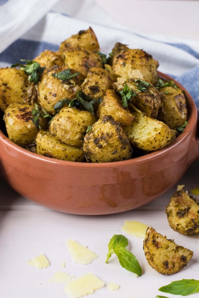 Pesto Potatoes in a small bowl with basil leaves